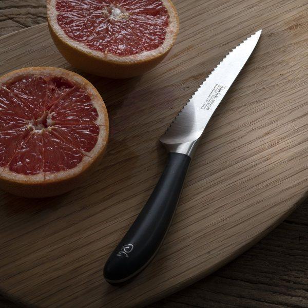 """12cm/4.5"""" Serrated Utility Knife on cutting board"""