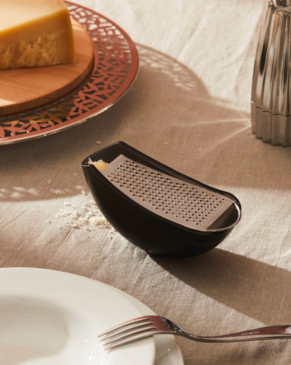 Alessi Grater with Cheese Cellar in black on a table with a block of cheese and a plate with fork