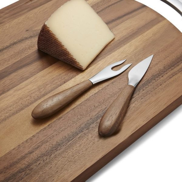 Nambe Curvo Cheese fork and knife pictured with cutting board and a wedge of cheese